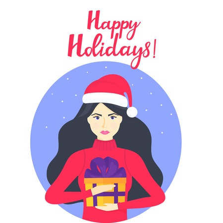 The girl in the cap of Santa Claus and in a warm winter sweater is holding a box with a gift. Happy holidays hand lettering Foto de archivo - 127268753