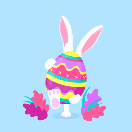 Easter bunny holding a big paschal egg. Funny rabbit walks on the lawn.