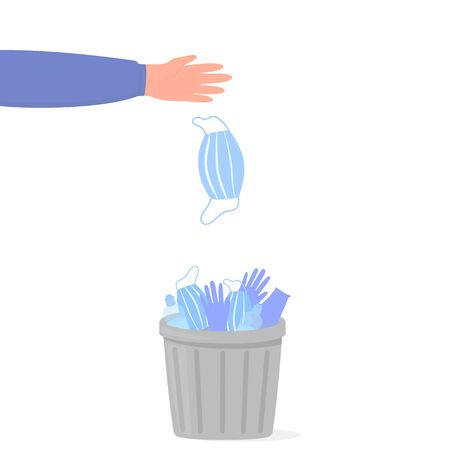 A hand throws a medical surgical mask into a trash can with used surgical gloves and sanitizers