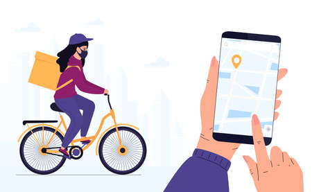 Delivery woman in a protective mask delivers parcel by bike. Track shipments using the mobile application.