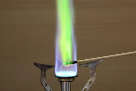 Ignition of copper oxide on a mini burner with a wooden stick. on the mini burner. Chemical experiments.