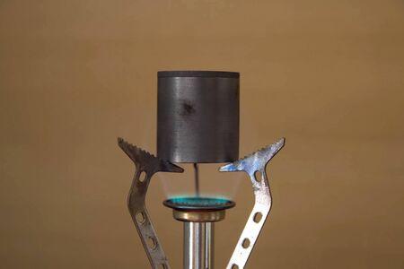 Melting metal on a mini burner. Chemical experiments.