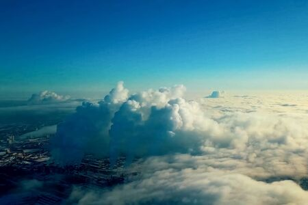 Top view above the clouds and the city, smoke from the pipes of plants and clouds. Stock fotó
