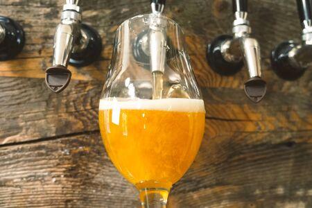 Aus dem Zapfhahn an der Bar Bier in ein Glas gießen. Bierabfüllung.