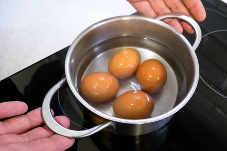 Boiled eggs in a pan are removed from the stove.