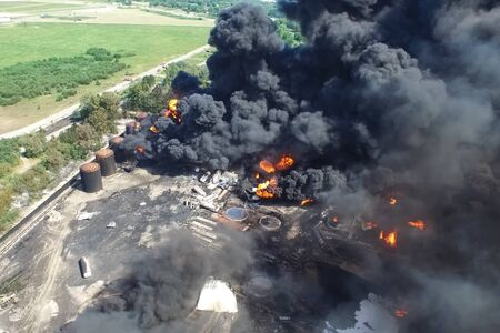 Oil storage fire. The tank farm is burning, black smoke is the combustion of hydrocarbons.