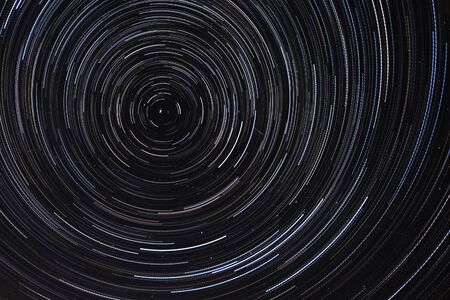 Long exposure starry sky, twisted tracks of stars. Starry sky background picture of stars in the night sky and the Milky Way.