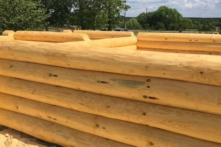 Drying and assembly of a wooden log house at a construction base. Preparation of logs for the assembly of the structure. Materials for a wooden house.