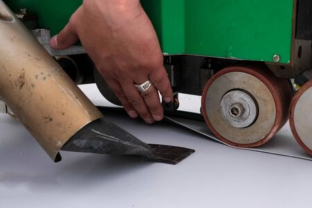 The mechanism for laying and gluing sheets of roofing polymer. Adhesion of polymer roofing sheets.