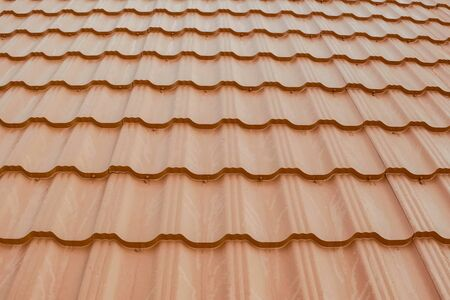 Modern roof made of metal. Corrugated metal roof and metal roofing. House with an orange metal roof. Stock fotó - 134741293