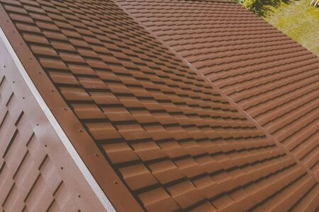 Modern roof made of metal. Brown metal tile on the roof of the house. Corrugated metal roof and metal roofing.
