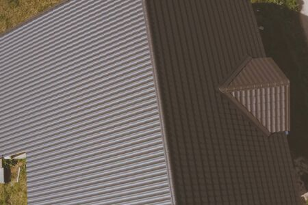 Modern roof made of metal. Brown metal tile on the roof of the house. Corrugated metal roof and metal roofing. Stock fotó - 134733174