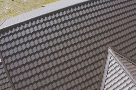 Modern roof made of metal. Brown metal tile on the roof of the house. Corrugated metal roof and metal roofing. Stock fotó - 134733175