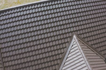 Modern roof made of metal. Brown metal tile on the roof of the house. Corrugated metal roof and metal roofing. Stock fotó - 134733177
