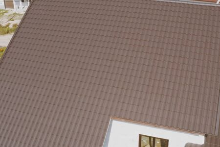 Modern roof made of metal. Brown metal tile on the roof of the house. Corrugated metal roof and metal roofing. Stock fotó - 134733179