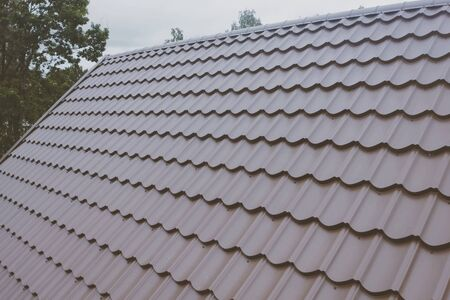 Modern roof made of metal. Brown metal tile on the roof of the house. Corrugated metal roof and metal roofing. Stock fotó - 134741935