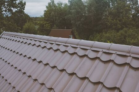 Modern roof made of metal. Brown metal tile on the roof of the house. Corrugated metal roof and metal roofing. Stock fotó - 134741947