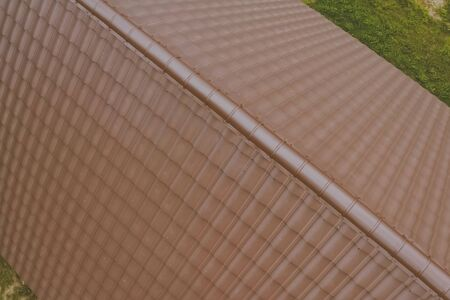 Modern roof made of metal. Brown metal tile on the roof of the house. Corrugated metal roof and metal roofing. Stock fotó - 134742747