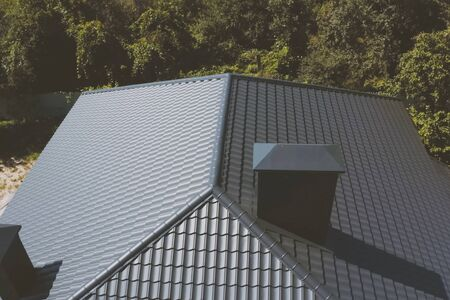 Modern roof made of metal. Gray-blue metal roof tiles on the roof of the house. Corrugated metal roof and metal roofing.
