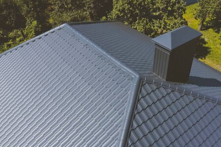 Modern roof made of metal. Gray-blue metal roof tiles on the roof of the house. Corrugated metal roof and metal roofing. Stock fotó - 134740628