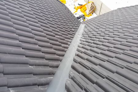 Modern roof made. Installation of the roof of the house from ceramic black tiles. Installation of tiles on the roof. Stock fotó - 134740637