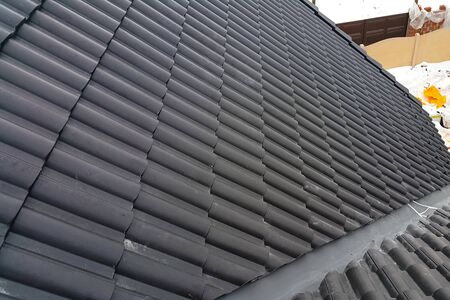 Modern roof made. Installation of the roof of the house from ceramic black tiles. Installation of tiles on the roof. Stock fotó - 134740643