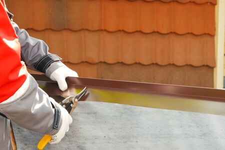 Worker shears a sheet of roofing metal. Scissors for metal. Stock fotó - 134740667