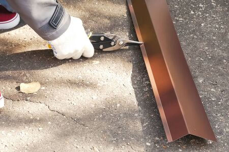 Worker shears a sheet of roofing metal. Scissors for metal. Stock fotó - 134740669