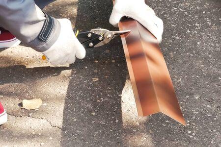 Worker shears a sheet of roofing metal. Scissors for metal. 写真素材