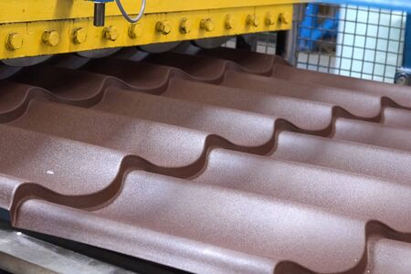 The process of stamping roofing metal on the machine. Plant of roofing materials.