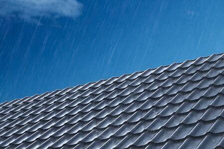 Regen ergießt sich auf die Metalldachziegel des Hauses. Regen auf dem Dach. Modernes Dach aus Metall. Wellblechdach und Metalldach. Standard-Bild