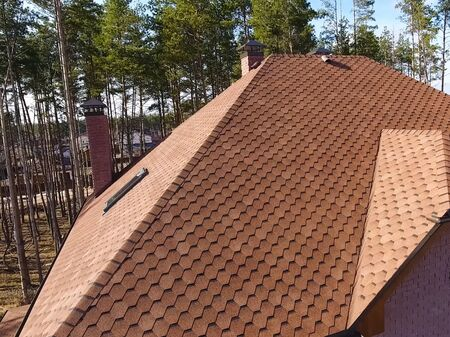 House with a roof from a bituminous tile. Bituminous tile for a roof. a roof from a bituminous tile. Stock fotó - 134740971