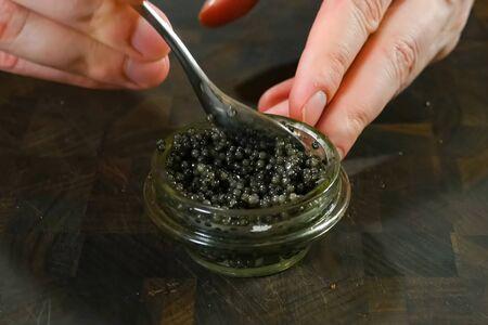 Stirring black caviar with a spoon in a glass jar.