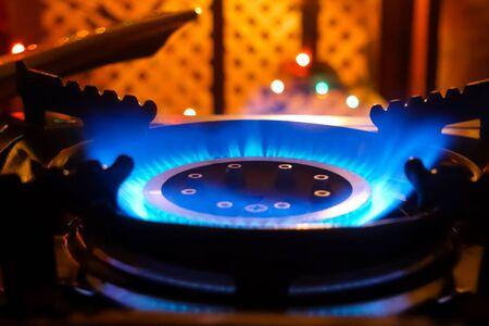 Cuisinière à gaz allumée. Flamme bleue d'un brûleur à gaz.