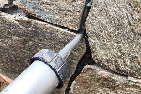Chanter les interstices entre la pierre sauvage sur le parement de la fondation. Face aux fondations d'une maison