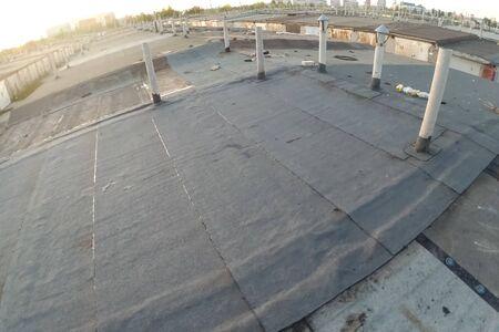 Dacheindeckung aus Dachpappe und Harz. Abdichtung von Dachmaterial auf dem Dach. Standard-Bild