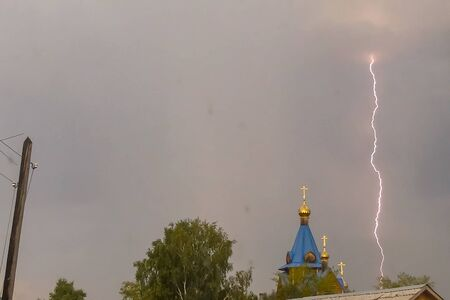 Lightning during a thunderstorm in the sky above the dome and cross of the church. Natural phenomenon of electricity, lightning.