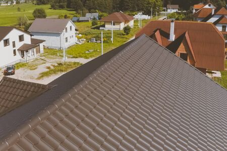 Modern roof made of metal. Brown metal tile on the roof of the house. Corrugated metal roof and metal roofing. Фото со стока
