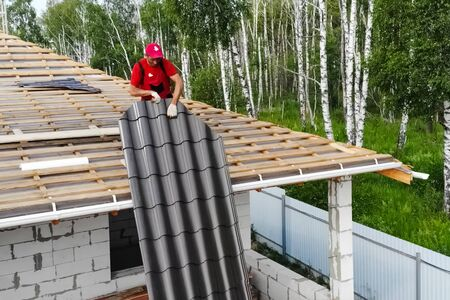 Moscow, Russia - August 23, 2017: Worker does the installation of the roof of the house. Installation of metal tiles, snow retainers and other elements of the roof.