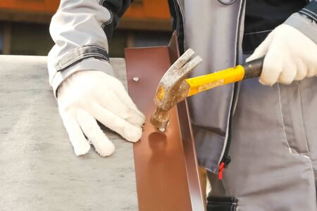 Nailing and hammering a sheet of roofing iron.