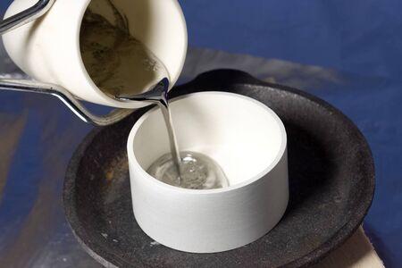 Pouring molten lead in ceramic ware. Heat-resistant ceramics Фото со стока