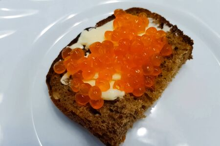 Sandwich with butter and red caviar on a plate.