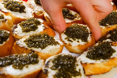 Sandwiches from a loaf with black caviar. Dear black caviar. 免版税图像