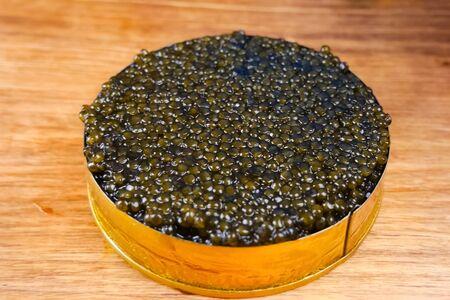Black caviar in a cardboard box. Spooning black caviar. Zdjęcie Seryjne