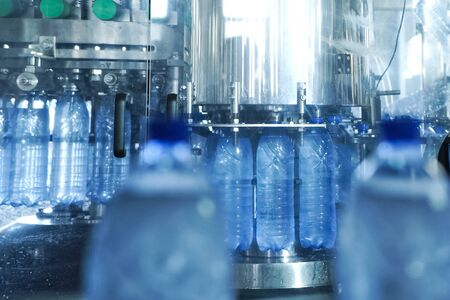 Filling line of sparkling water in a pet bottle. Mini factory for bottling water.