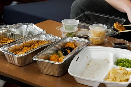 Food in plastic containers on the table. rolls, biscuits and salad.