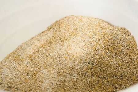 Ground barley in a container, grinding barley.