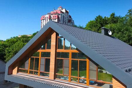 Dom z szarym metalowym dachem i dużymi oknami na elewacji. Nowoczesny dach wykonany z metalu. Dach z blachy falistej i metalowe pokrycia dachowe.