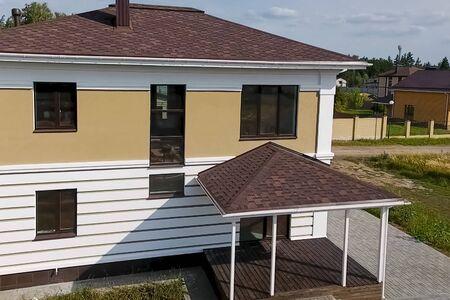 Huis met een dak van een bitumineuze tegel. Nieuw bakstenen huis. Bitumineuze tegel voor een dak. een dak van een bitumineuze dakpan. Stockfoto