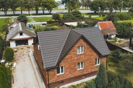 Modern roof made of metal. Corrugated metal roof and metal roofing. House with a brown metal roof. Zdjęcie Seryjne